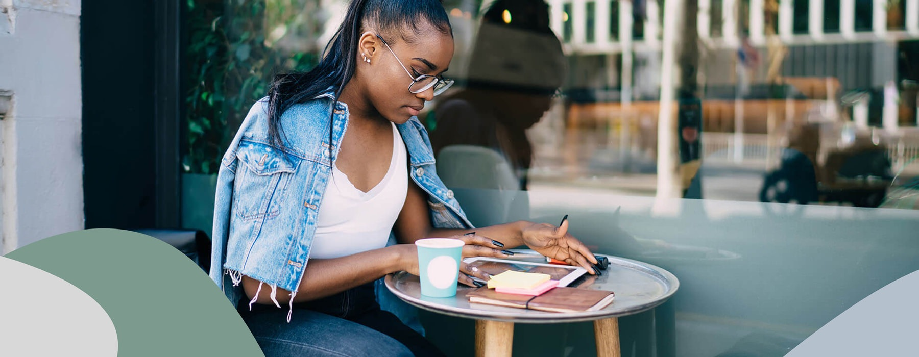 young woman works at a table outside a cafe